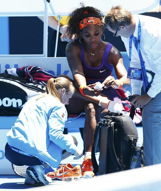 Lékařka (vlevo) ošetřuje kotník americké tenistce Sereně Williamsové během utkání prvního kola Australian Open v Melbourne.