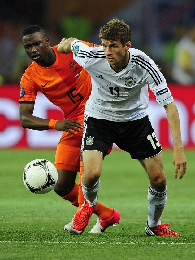 Thomas Müller (vpravo) v souboji s Jetrem Willemsem z Nizozemska