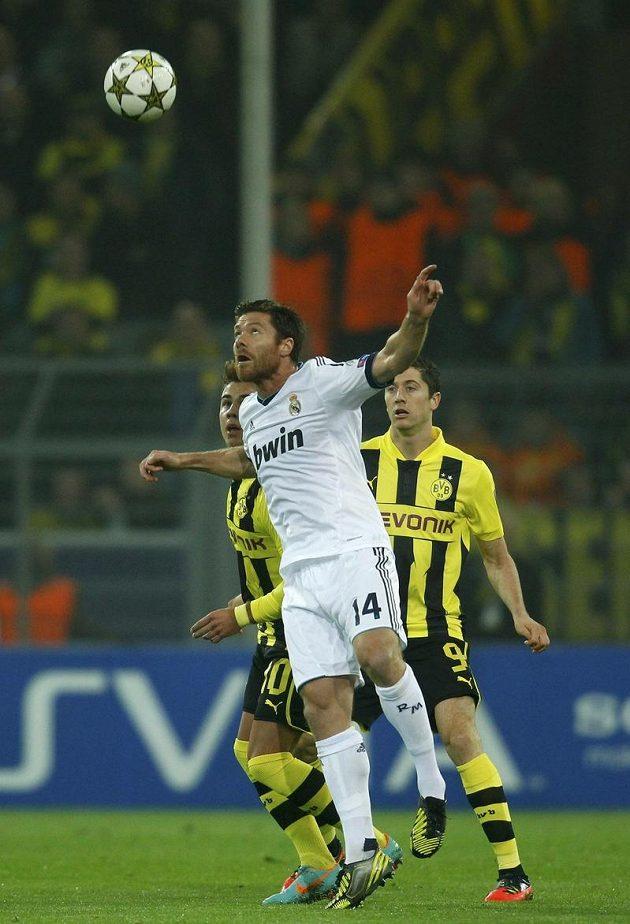 Záložník Realu Madrid Xabi Alonso odhlavičkoval míč před dvojicí fotbalistů Dortmundu Götze - Lewandowski.