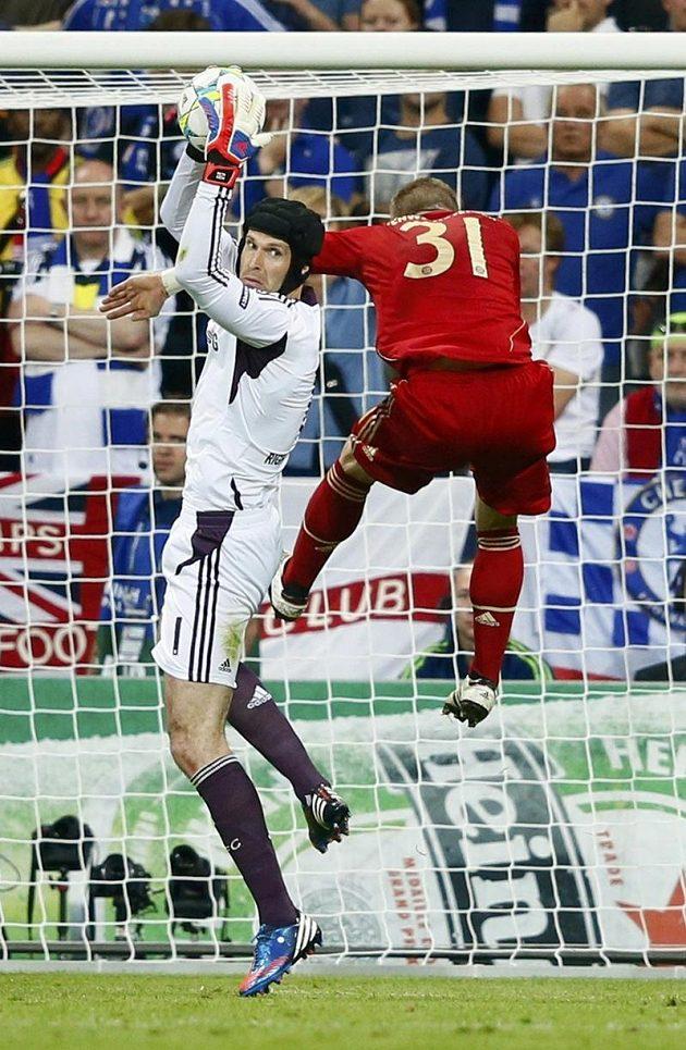 Brankář Chelsea Petr Čech chytá míč před Bastianem Schweinsteigerem z Bayernu Mnichov.