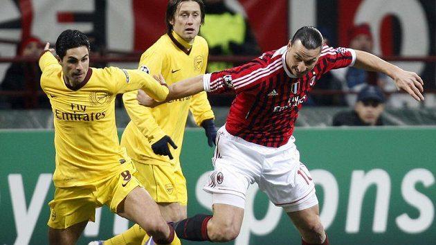 Tomáš Rosický (vzadu) z Arsenalu sleduje souboj Mikela Artety (vlevo) s útočníkem AC Milán Zlatanem Ibrahimovičem v osmifinále Ligy mistrů.