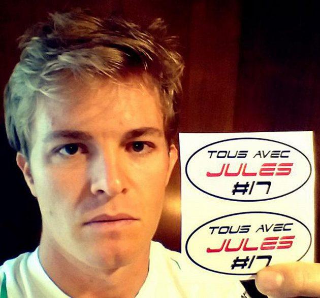 Nico Rosberg ukazuje nálepky se vzkazem Tous avec Jules (Všichni s Julesem), které budou mít jezdci vylepené v Soči na podporu svého těžce zraněného kolegy.