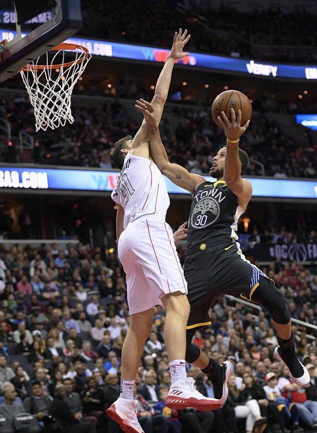 Hvězda Golden State Warriors Stephen Curry (30) se snaží prosadit ke koši přes bránícího Tomáše Satoranského z týmu Washington Wizards v utkání NBA.