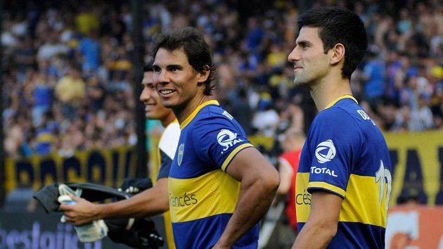 """Novak Djokovič (vpravo) a Rafael Nadal na zaplněném stadiónu La Bombonera. V pozadí je brankář """"Xeneizes"""" Sebastián D'Angelo."""