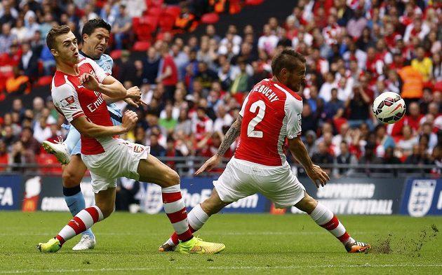 Nasri z Manchesteru City střílí, blokují ho Calum Chambers (vlevo) a Mathieu Debuchy z Arsenalu.