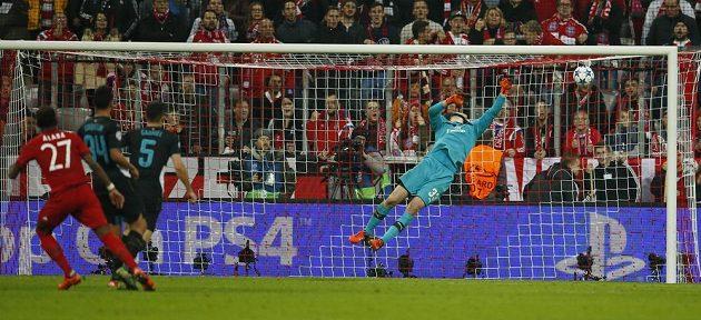 Gólman Arsenalu Petr Čech inkasuje po střele David Alaby z Bayernu Mnichov v Lize mistrů.