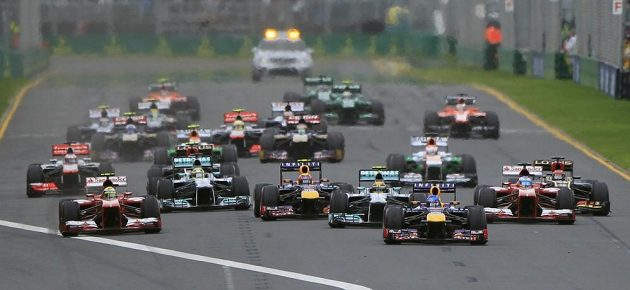 Sebastian Vettel s vozem Red Bull (třetí zprava) vede jezdecké pole po startu Velké ceny Austrálie.