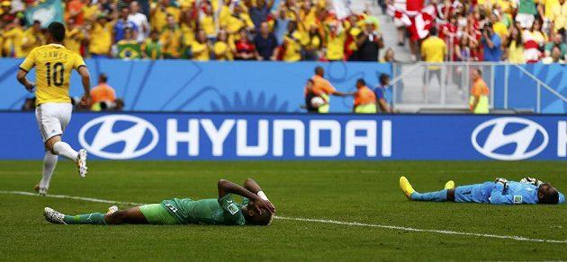 Geoffroy Serey Die (uprostřed) a brankář Boubacar Barry (vpravo) z Pobřeží slonoviny po druhém kolumbijském gólu, který dal Juan Quintero (není na snímku), vlevo je James Rodriguez.