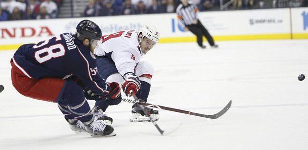 Denis Savard z Columbusu Blue Jackets odpálil puk před Dmitrijem Orlovem z Washingtonu v utkání 1. kola play off NHL.