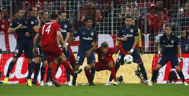 Xabi Alonso (14) dává vedoucí gól Bayernu - i s přispěním teče Josého Giméneze z Atlétika Madrid (druhý zprava).