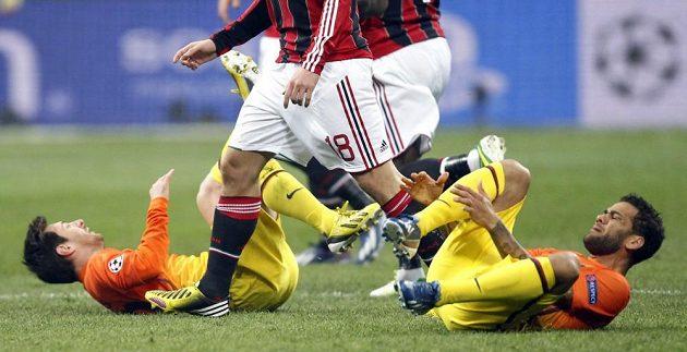Lionel Messi (vlevo) i jeho spoluhráč Daniel Alves z Barcelony leží na zemi po zákrocích fotbalistů AC Milán.