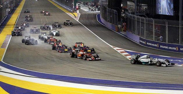 Lewis Hamilton (zcela vpravo) přebírá po startu Velké ceny Singapuru vedení, jeho stájový kolega Nico Rosberg (na snímku uprostřed nahoře) musel po problémech s řazením v zahřívacím kole vyrazit na trať z boxové uličky.