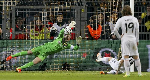 Brankář Dortmundu Roman Weidenfeller chytá penaltu Angelu di Maríovi z Realu v odvetě čtvrtfinále Ligy mistrů.