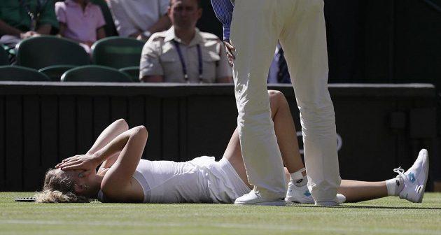 Česká tenistka Kateřina Siniaková leží s bolestnou grimasou na trávě ve Wimbledonu.