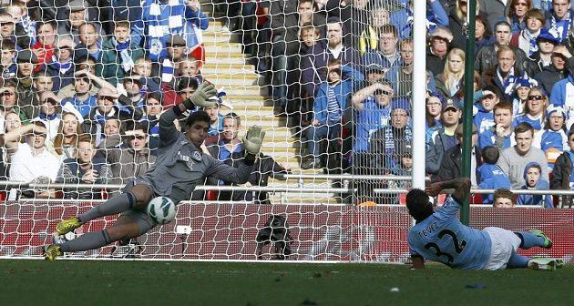 Brankář Wiganu Joel Robles chytá střelu Carlose Téveze z Manchesteru City.