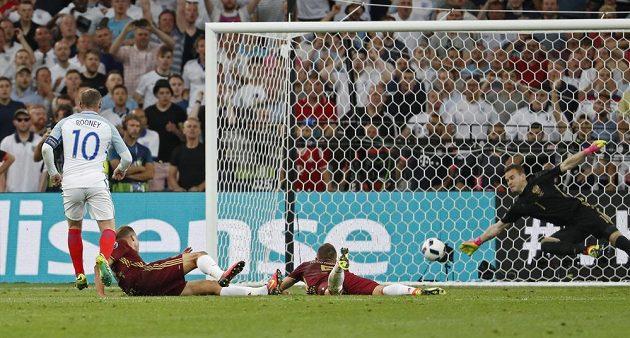 Ruský gólman Igor Akinfejev vyráží střelu Waynea Rooneyho na břevno.
