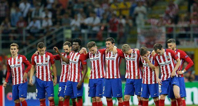 Zklamaní hráči Atlétika jen přihlíží, jak se jeho městští rivalové radují a laskají s pohárem pro vítěze Ligy mistrů.