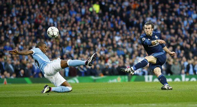 Gareth Bale střílí obávanou levačkou přes bránícího Fernandinha z týmu Manchesteru City.