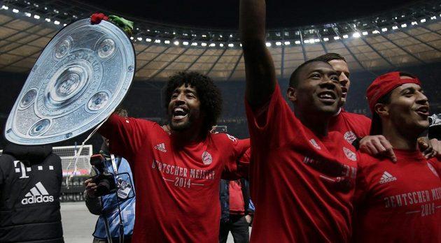 Zleva obránce Dante s trofejí, levý bek Alaba a záložník Thiago slaví 24. mistrovský titul Bayernu.