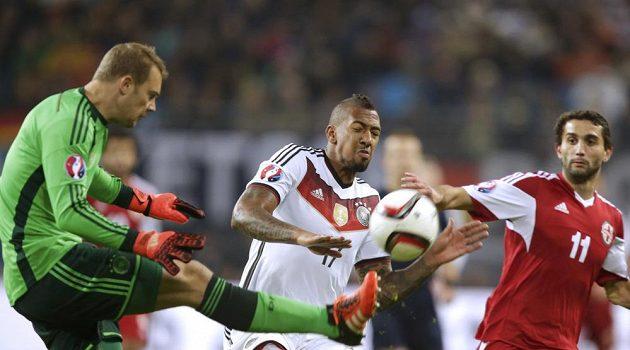 Brankář Nationalelf Manuel Neuer odvrací míč v zápase proti Gruzii. Uprostřed jeho spoluhráč Jerome Boateng, vpravo útočník Mate Vatsadze.