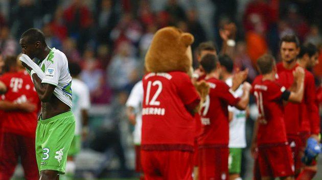 Smutný fotbalista Wolfsburgu Joshua Guilavogui (vlevo). V pozadí radující se fotbalisté Bayernu Mnichov.