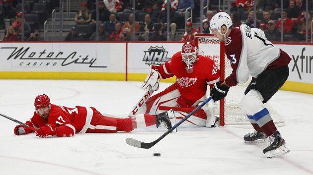 Český obránce Detroitu Red Wings Filip Hronek (17) sleduje z ledové plochy spolu s brankářem Jonathanem Bernierem (45) útočnou akci útočníka Colorada Valerije Nichuškina v utkání NHL.