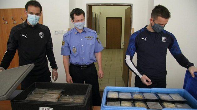 Asistent trenéra fotbalové Viktorie Marek Bakoš (vlevo) se záložníkem Janem Kopicem předávají obědy jednohomu z městských strážníků v Plzni.