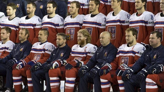 Čeští hokejisté poslouchají pokyny při oficiálním fotografování na tréninku.