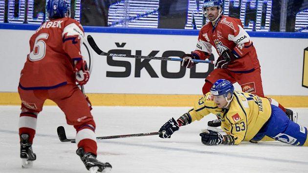Čeští hokejisté Jakub Jeřábek (5) a Michal Řepík nad vleže bojujícím Švédem Fredrikem Handemarkem.