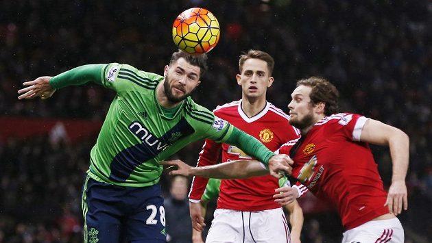 Útočník Charlie Austin z Southamptonu v souboji s Dannym Blindem z Manchesteru United v zápase 23. kola anglické Premier League.