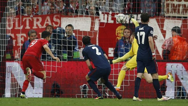 Robert Lewandowski uklízí míč za záda brankáře Atlétika Madrid Jana Oblaka.