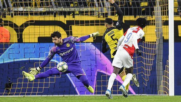 Brankář Dortmundu Roman Bürki zneškodnil šanci Slavie po hlavičce Petera Olayinky (vpravo).