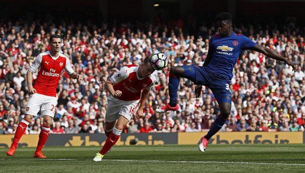 Fotbalista Arsenalu Rob Holding odehrává hlavou míč před hráčem Manchesteru United v utkání Premier League.