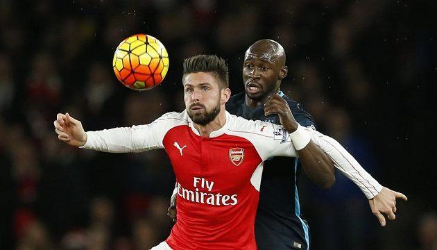 Olivier Giroud (vlevo) z Arsenalu bojuje o míč s Eliaquimem Mangalou z Manchesteru City.