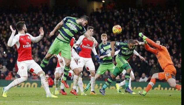 Ashley Williams (druhý zprava) ze Swansea překonává Petra Čecha v bráně Arsenalu.