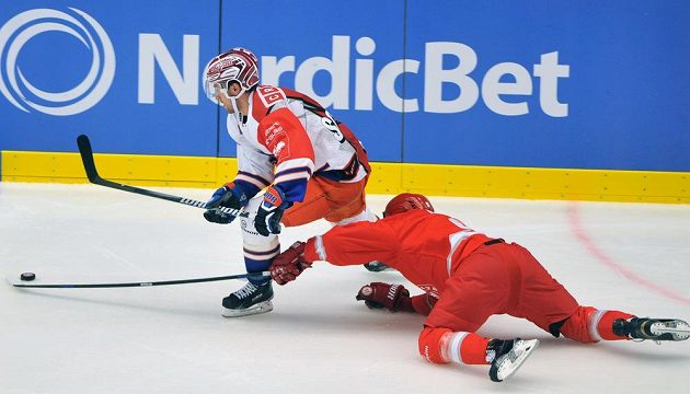 Třinecký obránce Denis Kindl (vpravo) se snaží vypíchnout puk Davidu Kolomatisovi z Tampere.