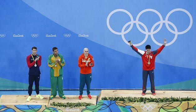 Zleva Michael Phelps, Chad Le Clos a Laszlo Cseh se tísní na stupni pro držitele stříbrné medaile. Vpravo vítěz Joseph Schooling.