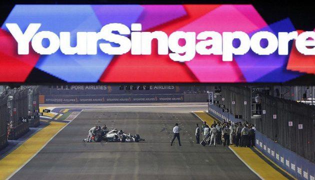 Pořadatelé tlačí vůz Nika Rosberga zpět do boxové uličky poté, co německý pilot Mercedesu během zahřívacího kola Velké ceny Singapuru kvůli problémům s řazením zůstal stát na trati.