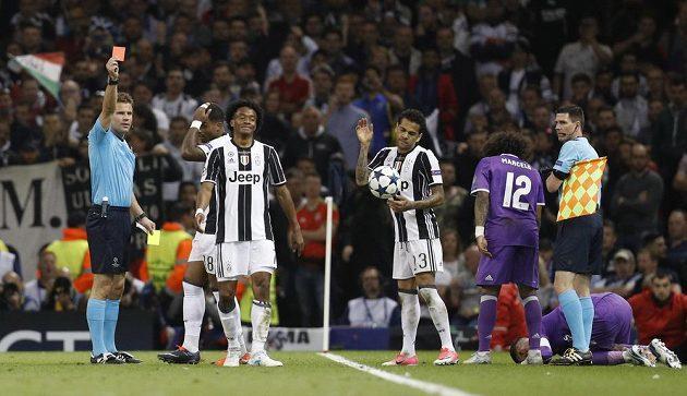 Rozhodčí Felix Brych ukazuje červenou kartu Juanovi Cuadradovi z Juventusu. Vpravo klečí na trávníku zadák Realu Sergio Ramos.