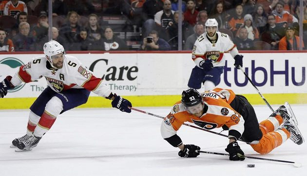 Bojovník Jakub Voráček z Philadelphie v pádu během prodloužení zápasu NHL s Floridou Panthers. Vlevo Aaron Ekblad z Floridy. Díky nájezdu Voráčka vyhráli Letci 2:1.