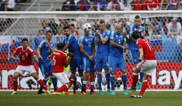 Gareth Bale obstřeluje slovenskou zeď a překonává gólmana Kozáčika.