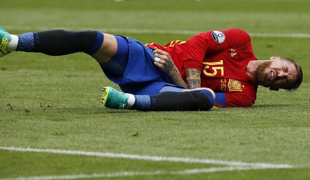 Španělský zadák Sergio Ramos se svíjí s bolestivou grimasou na trávníku.