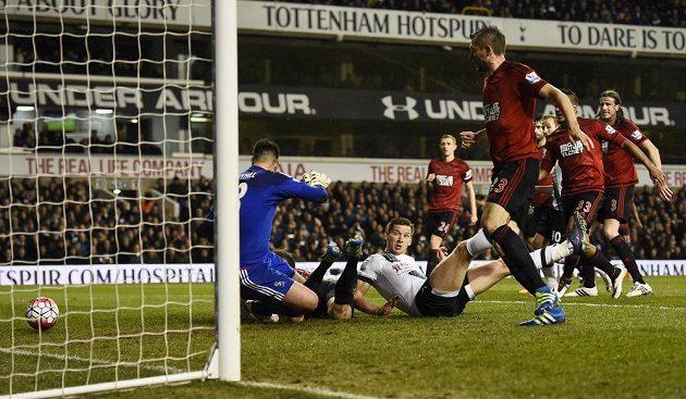 Fotbalista West Bromwiche Craig Dawson schovaný za brankářem West Bromwiche Boazem Myhillem poslal do vlastní brány míč, jehož dráhu sleduje Jan Vertonghen z Tottenhamu.