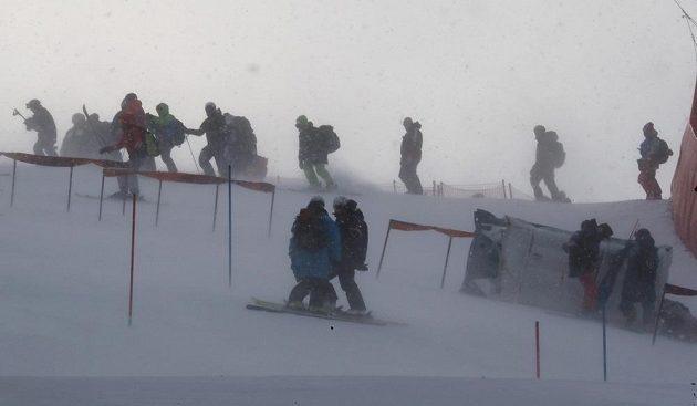 Pracovníci technické čety čelí nepříznivým povětrnostním podmínkám při přípravě olympijského závodu žen ve slalomu.