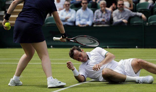 Radek Štěpánek se zvedá z trávy po pádu v prvním kole Wimbledonu.