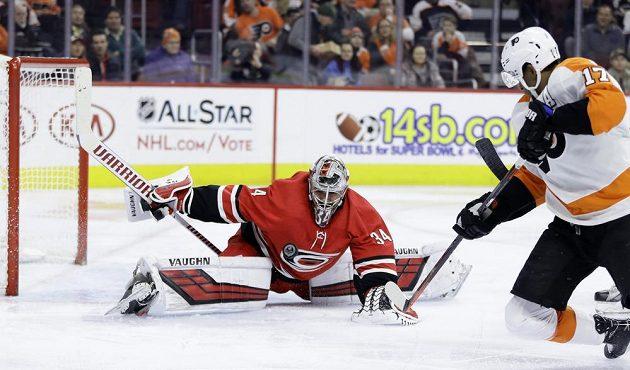Gólman Caroliny Hurricanes Petr Mrázek v akci, likviduje šanci Simmondse z Philadelphie v utkání NHL.