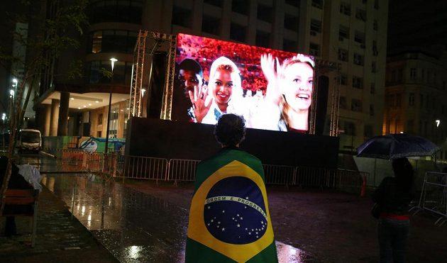 Žena sledující slavnostní zakončení v nepříznivém počasí v centru Ria.