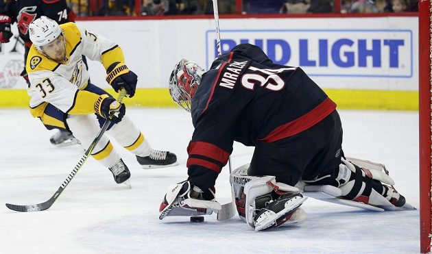 Švédský hokejista Viktor Arvidsson (33) z týmu Nashville Predators pálí na Petra Mrázka v brance Caroliny Hurricanes.