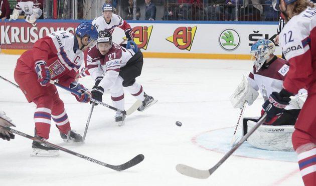 Kapitán národního týmu Tomáš Plekanec (vlevo) střílí svůj druhý gól lotyšskému brankáři Edgarsi Masalskisovi (vpravo).