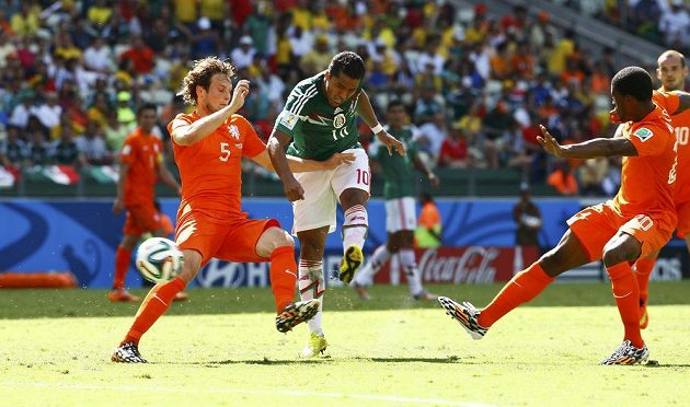 Giovani Dos Santos mezi Daleym Blindem (vlevo) a Georginiem Wijnaldumem střílí vedoucí gól Mexika v osmifinálovém duelu s Nizozemskem.